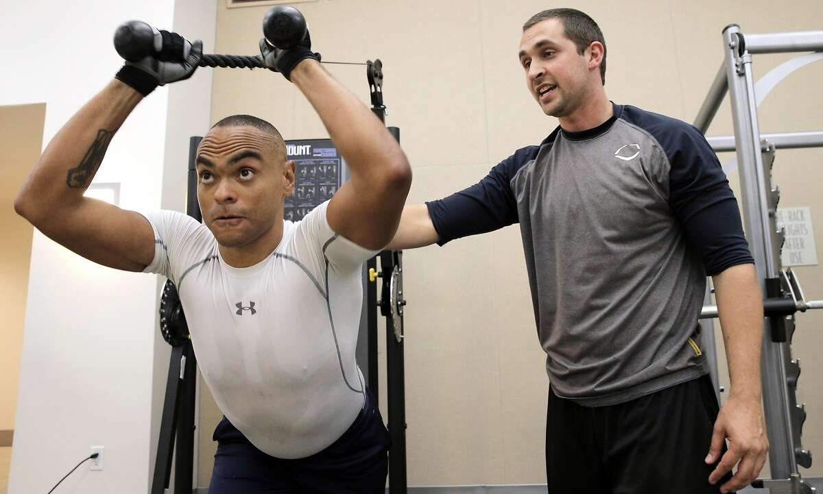 Baron Lambert, right, works with his client, Chris Barbour, at Barbour's condominium gym in San Francisco, Calif., on Wednesday, October 5, 2016. Lambert left his regular job as a fitness trainer at 24-Hour Fitness to go into business for himself, similar to many americans in recent years.