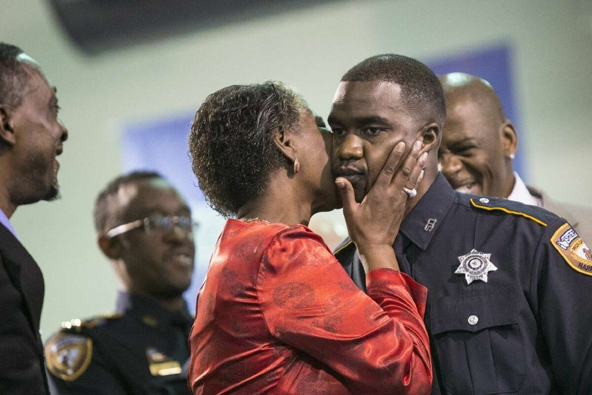 A graduate receives a kiss from his mother during a graduation ceremony for 32 Harris County Sheriff's Office Academy cadets Nov. 21 at the HCSO Academy and Gun Range in Humble.