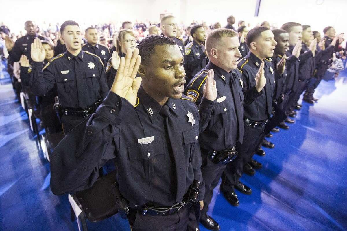 Brian Bishop recites a ceremonial oath of office with his fellow graduates during a graduation ceremony for 32 Harris County Sheriff's Office Academy cadets Nov. 21 at the HCSO Academy and Gun Range in Humble.