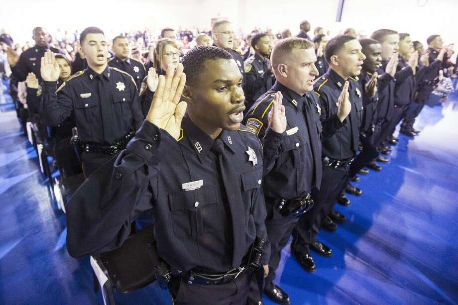 Brian Bishop recites a ceremonial oath of office with his fellow graduates during a graduation ceremony for 32 Harris County Sheriff's Office Academy cadets Nov. 21 at the HCSO Academy and Gun Range in Humble. Photo: ANDREW BUCKLEY