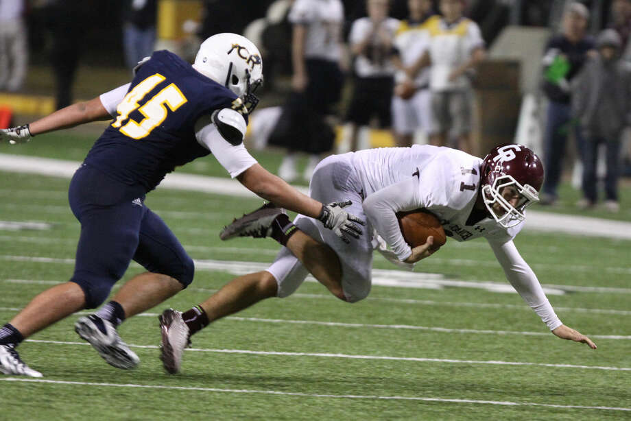 Cinco Ranch's Trent O'Donnell gets tripped up as he scrambles against Cypress Ranch's Trent Walker during the Class 6A Division I Football Area Playoffs at Berry Center Stadium in Cypress, Texas on Friday, November 21, 2014. Photo: Staff Photo By Alan Warren