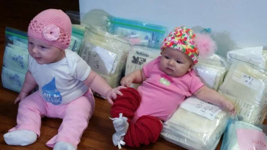 Breeana (left) and Elliott (right in hat) sit among the several packages of donated mother's milk at Kingwood Medical Center's donor depot Tuesday.