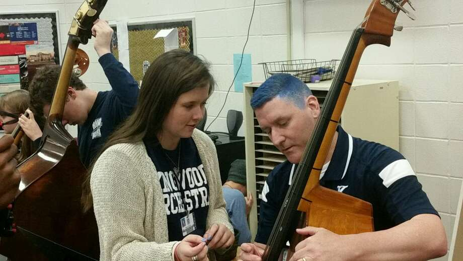 Kingwood High School senior Bailey Breuhl instructs KHS Principal Dr. Ted Landry how to play the bass during Bleed Blue day. Photo: Matthew Costa
