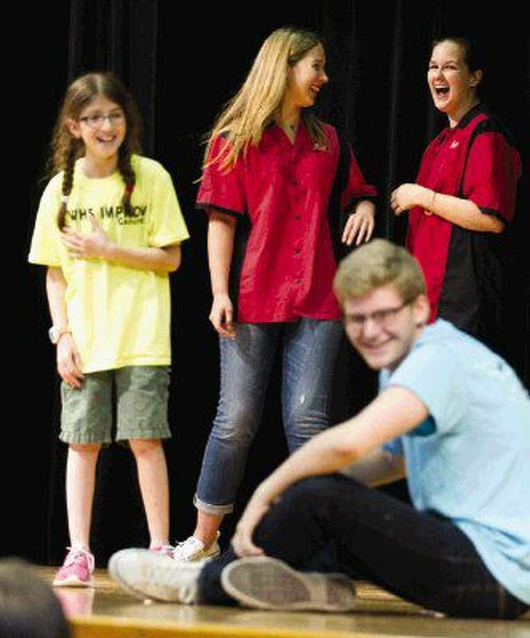 The Woodlands High School Improv Troupe members Katerina Meyerl, center, and Brenna Lelicah laugh as Mitchell Intermediate School students Rotem Rics and Jason Leach go through a skit at Mitchell Intermediate School Wednesday. Photo: Jason Fochtman