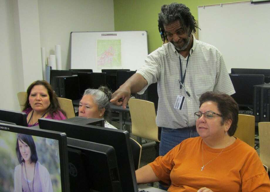 Lone Star College ESL instructor Mark Yorke works with Kroger employees (left to right) Maria Aguilera, Lilia Gutierrez and Luz Salcido to help improve their English skills. Photo: Submitted Photo