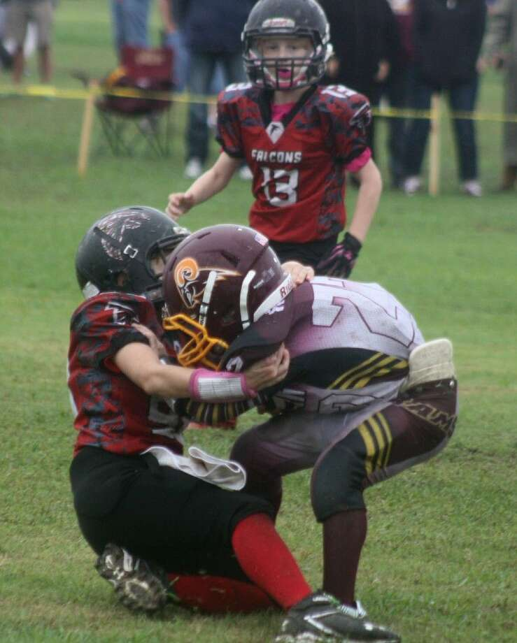 Reid Ridley hauls down Deer Park Rams running back Andrew Ramos for a four-yard loss during the second overtime Saturday afternoon. It was Ramos who forced the overtime with a last-minute TD. Looking on for the Falcons is Jacob Biddy (13). Photo: Robert Avery