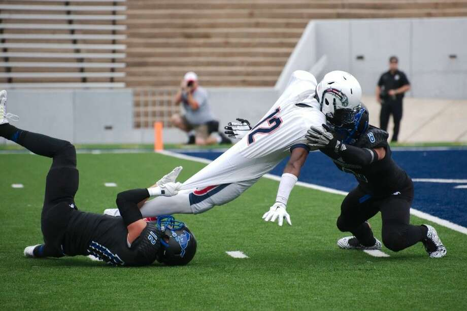 Friendswood's Nick Dehoyos (12) and Friendswood's Blake Rollen (8) try to keep Dawson's Brailon Mouton (12) out of the end zone Saturday at Rice Stadium. Dawson took a heart-stopping 28-26 win. Photo: KIRK SIDES