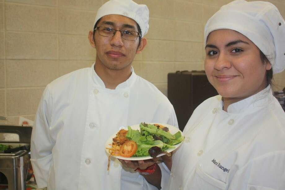 From left, Gilberto Olivares and Maria Rangel, two of the food preparers from the kitchen of PISD's new Career and Technical High School, show what was waiting for the tastebuds in the Phillips Fieldhouse hospitality room Saturday afternoon. Spaghetti with chicken, a tossed salad and rolls. The two, along with the numerous other students, spent hours in the hospitality room and back at the high school preparing numerous dishes for referees, coaches, scouts and school officials. Photo: Robert Avery