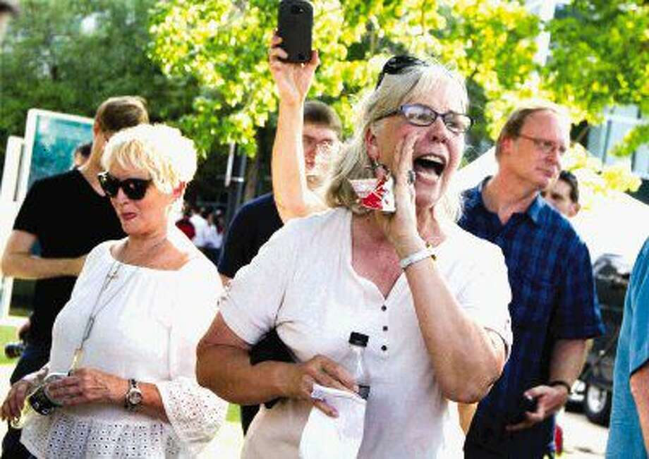 Cyndy Coker shouts at protesters before a political rally for presumptive Republican nominee Donald Trump at The Woodlands Waterway Marriott Hotel & Convention Center Friday.