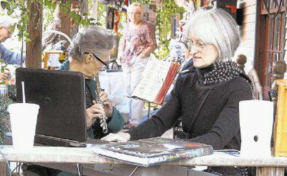 Helen Christine Bloomquist (left) and Lisa Schumaker (right) play soothing music during the Sue Ferguson Memorial fund. Photo: Jacob McAdams