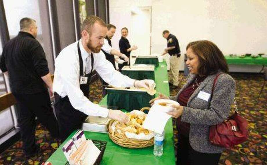 Montgomery County Assistant District Attorney Tyler Dunman serves soup to Michelle Harris during the Empty Bowls Luncheon on the top floor of the Conroe Tower Wednesday, which raised funds for the Montgomery County Homeless Coalition. To view or purchase this photo and others like it, visit HCNpics.com.