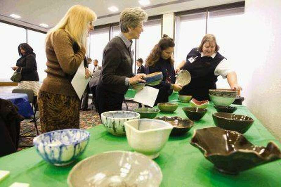 Women admire hand crafted bowls for sale made by members of the Conroe Art League and Lone Star College students during the Empty Bowls Luncheon on Wednesday at the Conroe Tower. The fundraiser benefits the Montgomery County Homeless Coalition. To view or purchase this photo and others like it, visit HCNpics.com.