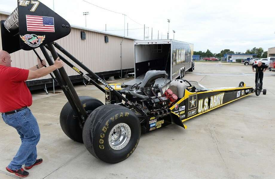 Automotive instructor Gary Miller and Schumacher Racing representative Todd Gauthier unload the U.S. Army dragster from the trailer on Nov. 6 at Cypress Creek High School. Photo: Submitted Photo