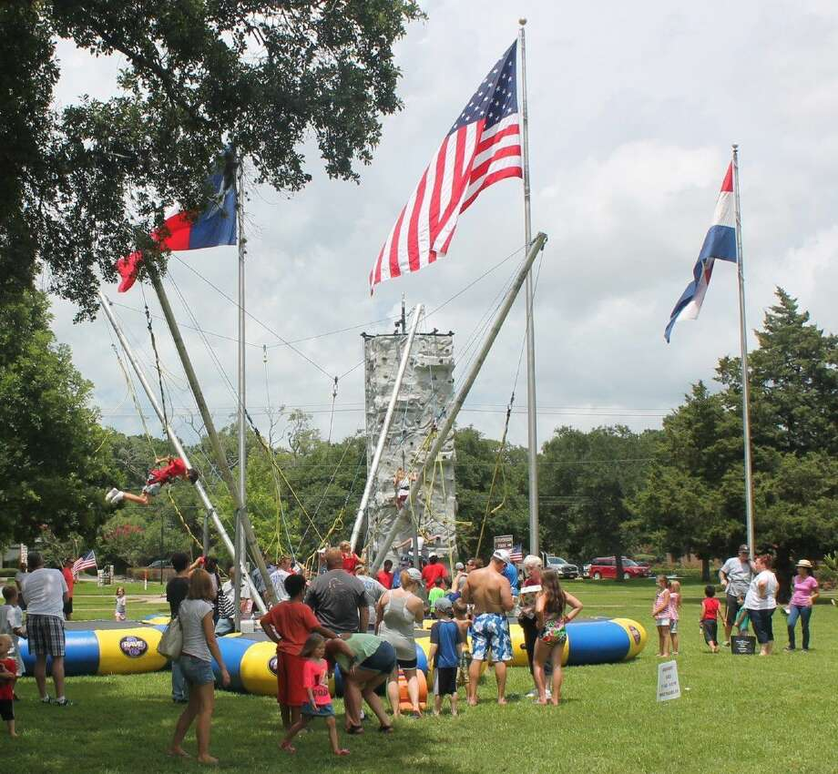 July 4th carnival rides in Stevenson Park include a train, rock wall, mechanical bull, and obstacle course.