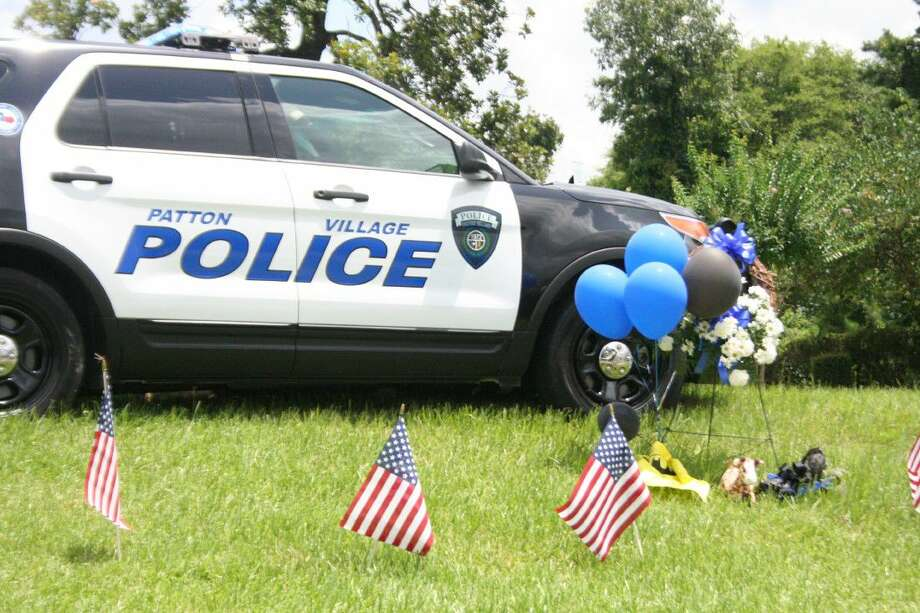 A police cruiser was parked in front of Patton Village Community Center for most of the day Monday, where residents placed tokens of remembrance.