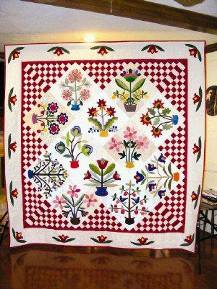 """The finished product of """"The Cut Ups"""" hand appliqued quilt named """"Flourishes"""" donated to the Humble ISD Council of PTAs to help raise funds for their Scholarship Fund at the Founder's Day Luncheon."""