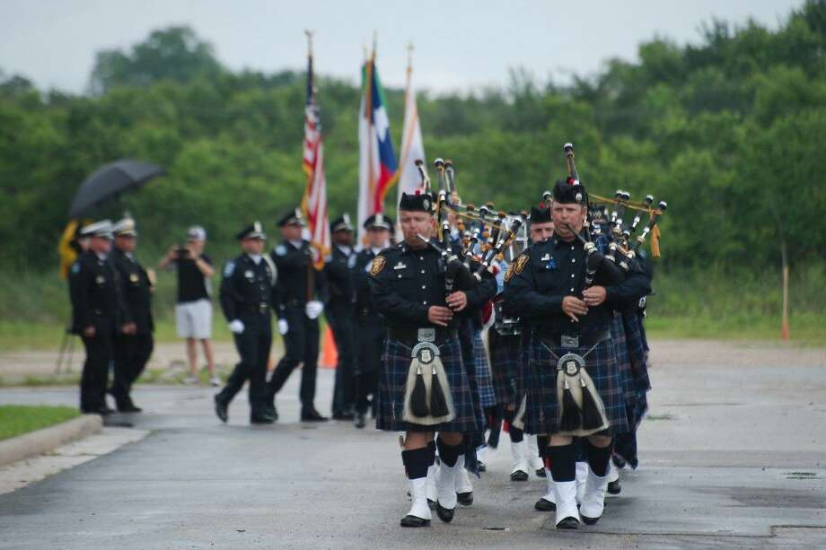 Fort Worth Pipes and Drums play bagpipes as they lead a procession escorting the body of fallen Pearland Police officer Endy Ekpanya during a service at Grace Community Church Tuesday, June 21. Photo: Kirk Sides