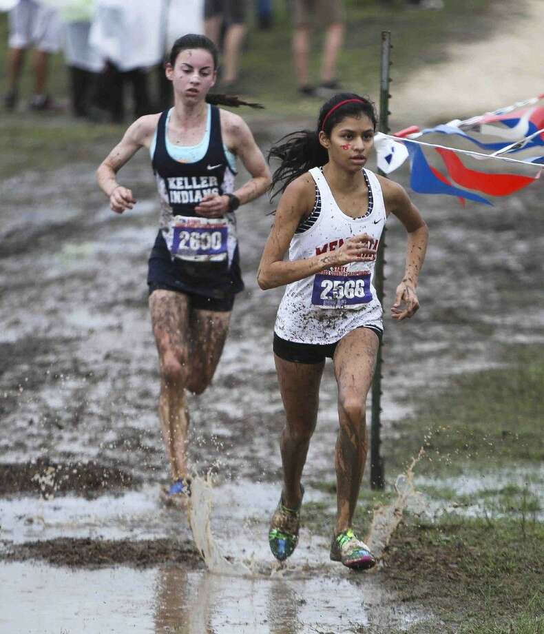 Memorial senior Khayla Patel and another runner power through a water hazard Saturday morning at the 6A state cross country meet in Round Rock. Patel is a veteran of the state meet, making her fourth appearance in four years and she finished fourth overall this year. To view more photos from the state meet, visit HCNpics.com. Photo: Jason Fochtman