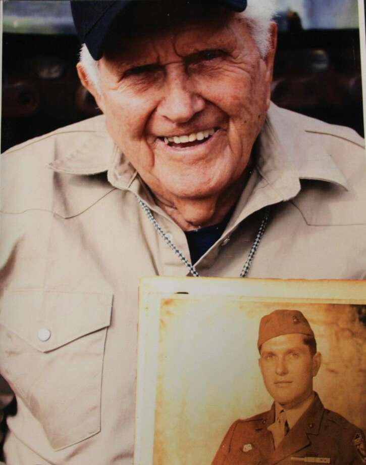 Troy D. Nolen holds a photo of his younger self during service in World War II. Nolen was assigned to the 1st Marine Division. Photo: Submitted
