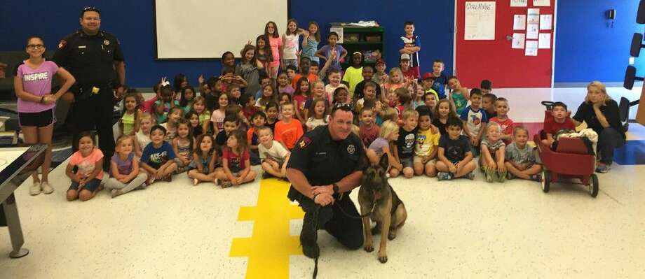 "Deputy Henson, center with his canine Rudo, and Deputy Guerra, left rear, with the Harris County Precinct 4 Constable's Office attend a show and tell day at ""Kid's Laughing and Learning Center"" on June 15 at 12217 Northpointe Blvd. Photo: Submitted Photo"