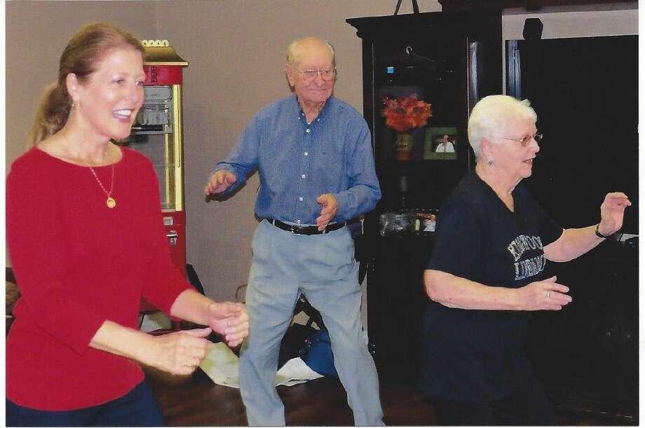 "Cheerful dancers Teddi Meyer and Pati Hendricks ""cut a rug"" with resident Walter Fuelberg."