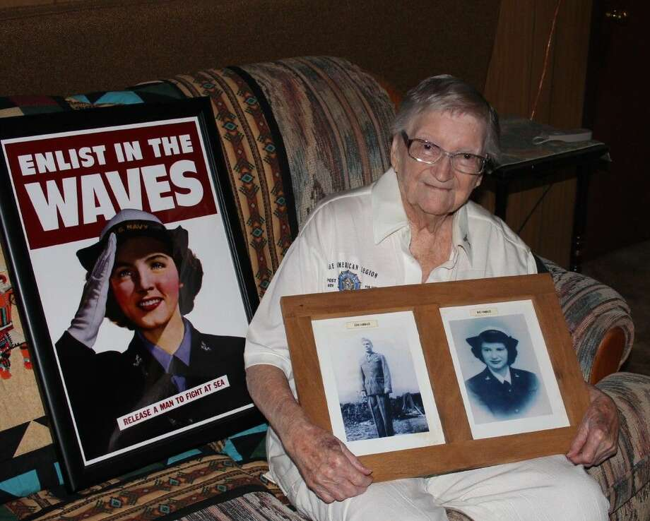 Mae Chenoweth Hammack holds a photo of herself from her time during World War II in the US Navy WAVES. She says a recruiting poster for the WAVES (pictured next to her) encouraged her to join. Photo: Vanesa Brashier
