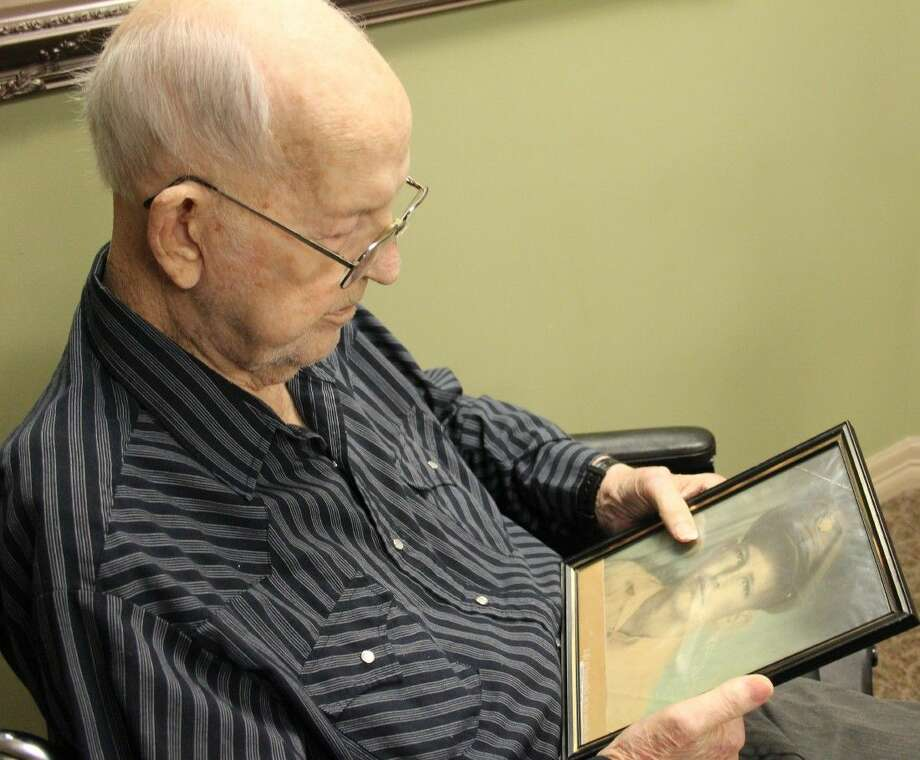 Preston Phillips looks at a photo of himself from World War II. Phillips worked as an airplane mechanic in England, keeping B-17s ready for bombing missions. Photo: Vanesa Brashier