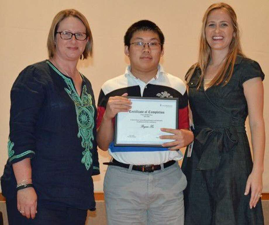 Project SEARCH intern Bryan Xu receives his graduation certificate from Angela Trahan, Chief Operations Officer, UnitedHealthcare Community Plan of Texas (left), and Project SEARCH teacher Leah Davis. Photo: Submitted Photo