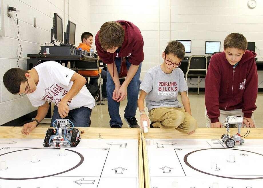"Pearland Junior High East students (from left) Cameron Sarro, Garrett Ellington, Zane Delehanty and Lance Ishimura test their robots during the after-school ""Building STEM through Robotics"" program."