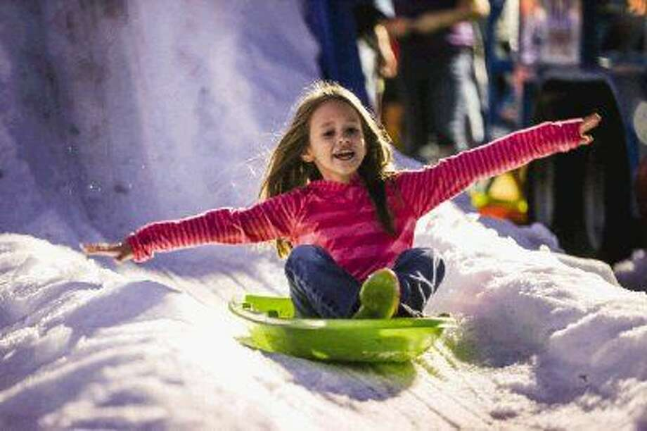 Seven-year-old Bella Sadler, of Magnolia, slides down a pile of snow during the International Winter On The Waterway on Sunday, Nov. 23, 2014, at Town Green Park. To view or purchase this photo and others like it, go to HCNPics.com. Photo: Michael Minasi