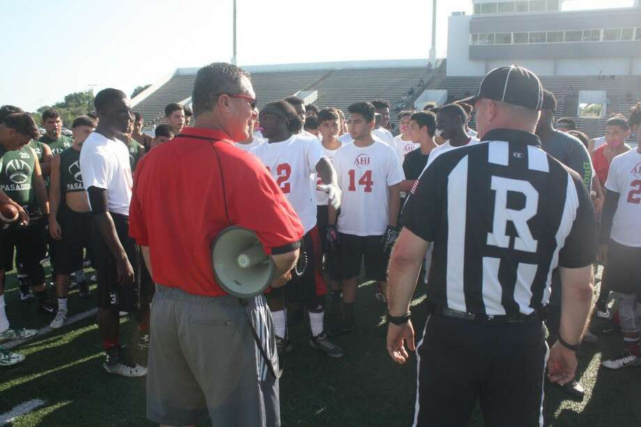 South Houston head football coach Dwayne Lane and a referee go over the ground rules with the 7-on-7 players prior to last week's competition. Photo: Robert Avery