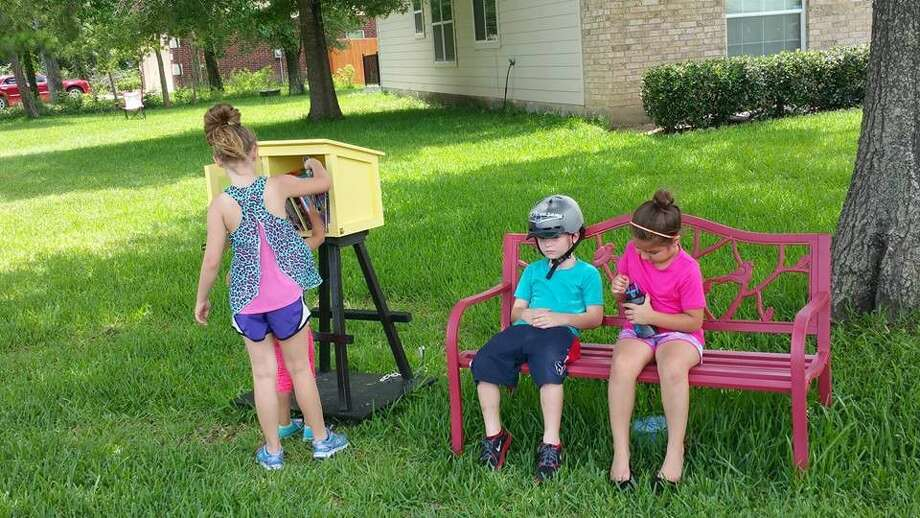 Children from the neighborhood stop to enjoy a book at Abby's Library during their family walk in Newport.