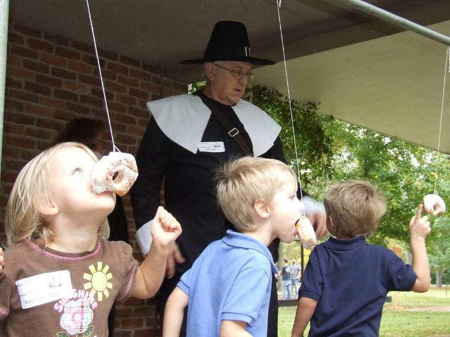 Courtney Spence (left), Joshua Spence, and Camden Spence race to eat a donut off a string at the Pilgrim Festival.