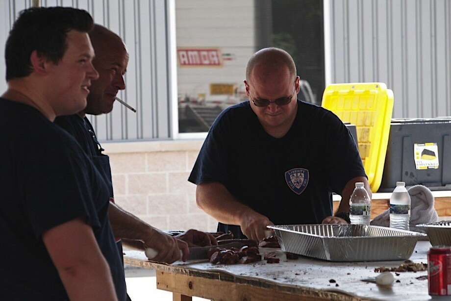 Liberty firemen cut up the last of the 3,000 pounds of meat the department sold in their barbecue fundraiser June 15-18. Photo: Casey Stinnett