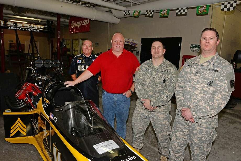 The Tony Schumacher U.S. Army dragster sits in the automotive bay at Cypress Creek High School on Nov. 6. Pictured, from left, are Todd Gauthier of Don Schumacher Racing, Cypress Creek automotive technology instructor Gary Miller and Staff Sgts. David Smith and Leo White of the U.S. Army. Photo: Submitted Photo