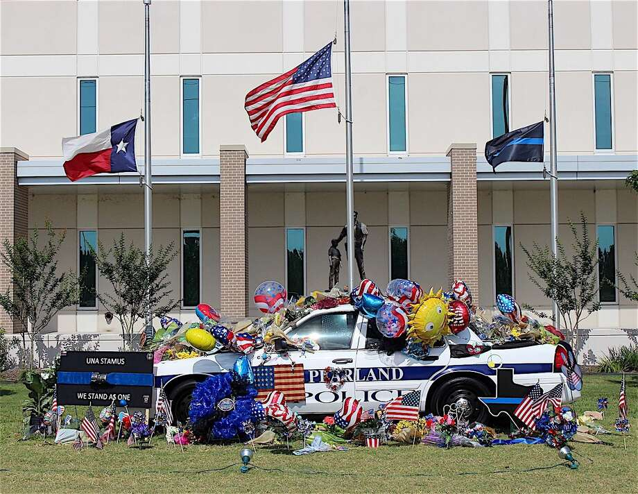 Flags fly at half staff and a police cruiser in front of Pearland Police Dept. headquarters is adorned with sympathy cards and flowers for Officer Endy Ekpanya and his family. Staff photo by Stacey Glaesmann