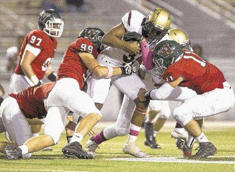 The Woodlands defensive linemen Michael Purcell and linebacker Zach La Canfora bring down Summer Creek quarterback John Holcombe.