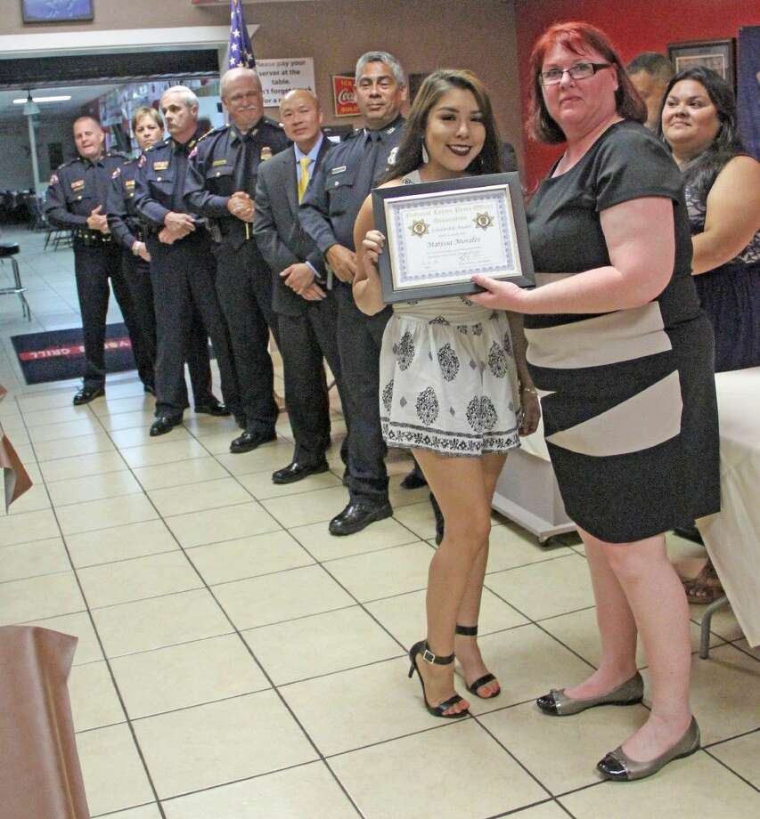 The Southeast Harris County Chapter of the National Latino Peace Officer Association hosted a Scholarship Banquet recently. Treasurer Kelly Sue Morgan (right) presents Marissa Morales with her scholarship recognition certificate. Photo: Kristi Nix