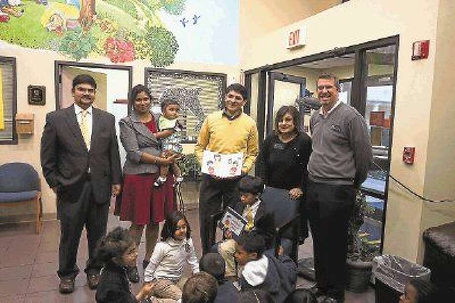 "Krishna Bhadriraju (seated) shows ""Krishna Saves a Bird"" to his peers, with (standing, left-right) his father Satish Bhadriraju, his mother Mani Bhadriraju holding younger brother Shreyshta, The Honor Roll pre-k art teacher and illustrator Guillermo Blanco, Early Childhood Program Principal Joy Dasgupta and Head of School Tom Heinly. Photo: Submitted"