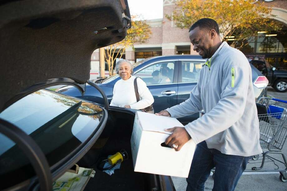 Former NFL player and Humble native Sammy Davis, right, helps Jessie Dailey load Thanksgiving dinner kits into her car during the 5th Annual Bird Bowl on Nov. 25, 2014, at Kroger in Humble. Each of the 75 local families received a kit containing a frozen turkey with various side dishes donated by Kroger. Photo: ANDREW BUCKLEY
