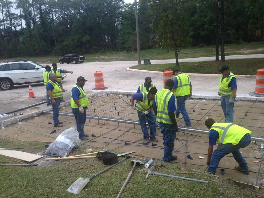 Workers repair and replace a section of Lake Woodlands Drive after a crew member discovered a large area after a leading storm drain cause the soil under the road to erode.