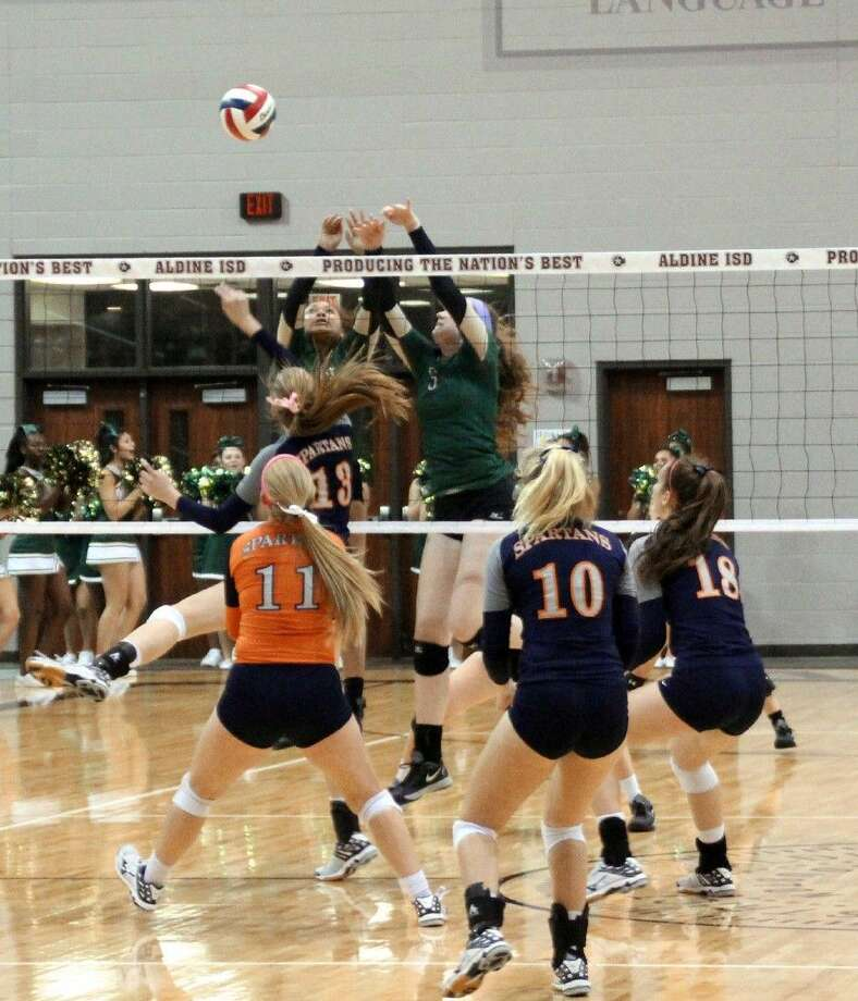 Cypress Falls volleyball players defend the net during the Golden Eagles' regional quarterfinal loss to Katy Seven Lakes on Nov. 10 at the Campbell Center in Aldine. The team finished its season as district champion and regional quarterfinalist.