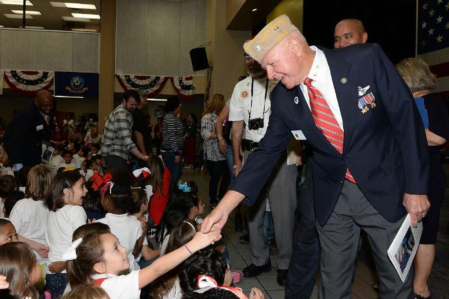 United States Marine Corps veteran John Heimburger shakes a student's hand at the Yeager Elementary School Veterans Day celebration on Nov. 6.