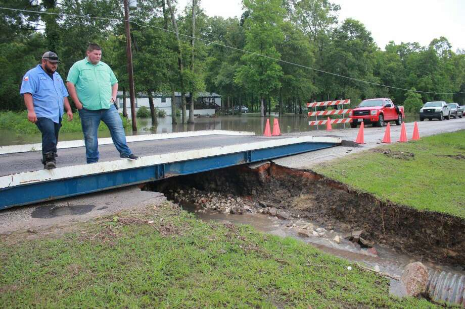 Josh Mitchell of Pct. 4 Road and Bridge and volunteer firefighter Bradley Templeton stand on the makeshift bridge over a damaged culvert on CR 67631 in the Woodland Hills community in Dayton on May 27, the morning after rains washed out the culvert. Photo: Vanesa Brashier