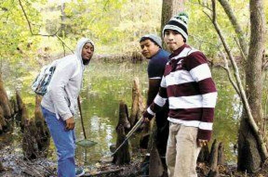 Quinton Coleman, Luis Alvarado, and Francisco Montes study living organisms found at Jesse Jones Park's Turtle Pond.