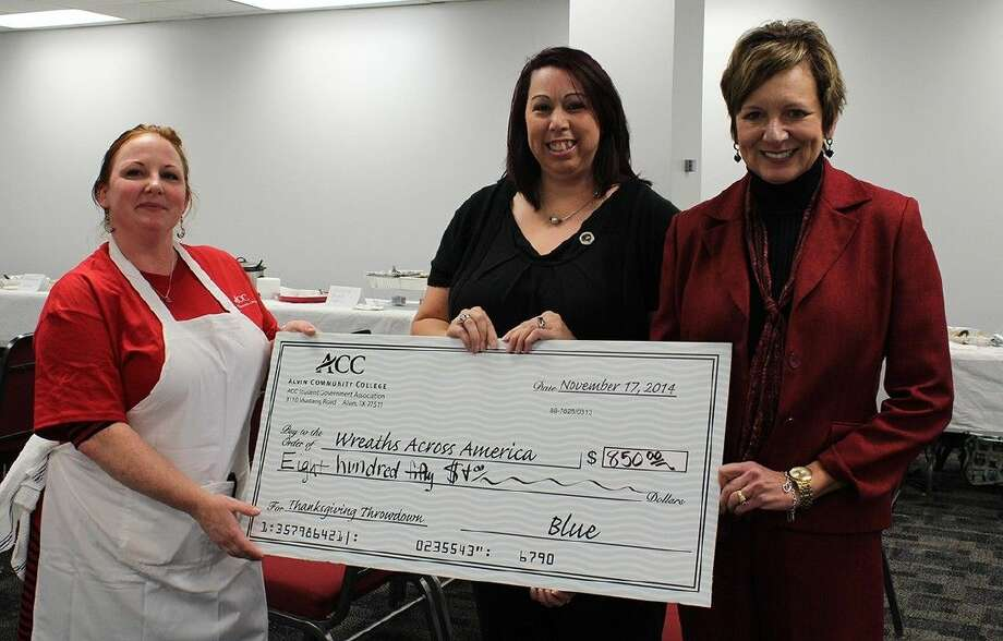 ACC SGA president Misty Jackson, left, and college president Dr. Christal M. Albrecht, right, present Sondra Moungey of Wreaths Across America with a check from the proceeds raised at the Thanksgiving Throwdown on November 17.