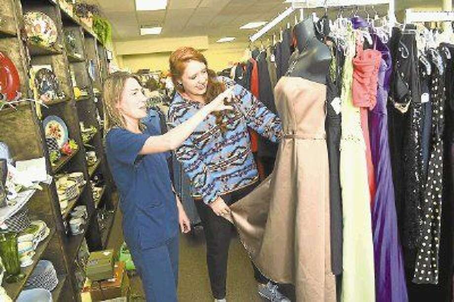 Store manager Meghan Mazerolle helps customer Zerica Zulpo shop for a dress at the resale shop. Photo: Tony Gaines