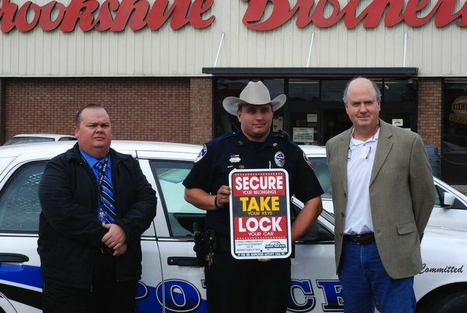 "Liberty Police Department Capt. Gary Martin, at left, and officer Drew Ries, center, were joined by Mark Hanna, Insurance Council of Texas public relations manager, to announce their ""Secure, Take, Lock"" initiative to encouraging holiday shoppers to take extra precautions with their valuable. Photo: Casey Stinnett"