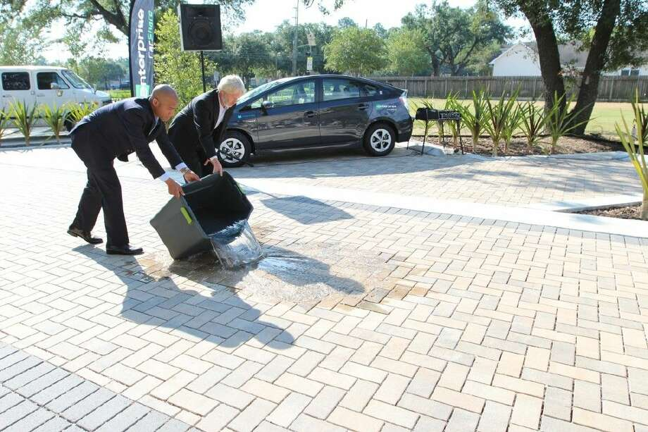 Energy Corridor District officials demonstrate the abilities of the permeable roadbed aspect of the woonerf project. The project earned the ECD the Mayor's Proud Partners award this past October.