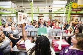 Latasha Alsbrooks, Volunteer Services Supervisor at the Houston Food Bank, instructs employees of Houston Community Newspapers & Media in how to sort donated items at the Houston Food Bank on Thursday.